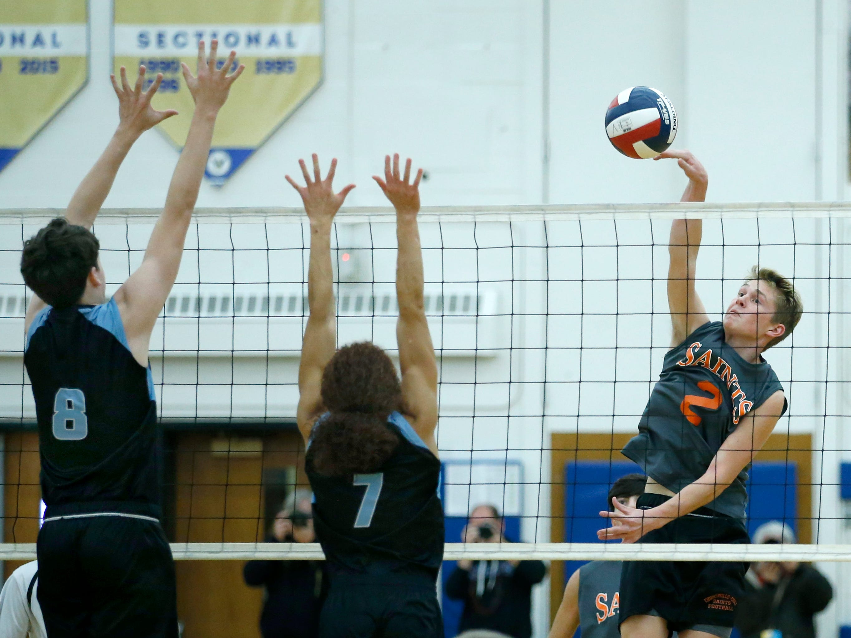 Class B volleyball final: Churchville-Chili's John Keele attacks against Midlakes' Kyle McCann and Isaiah Delgado in the first set at Webster Schroeder High School.