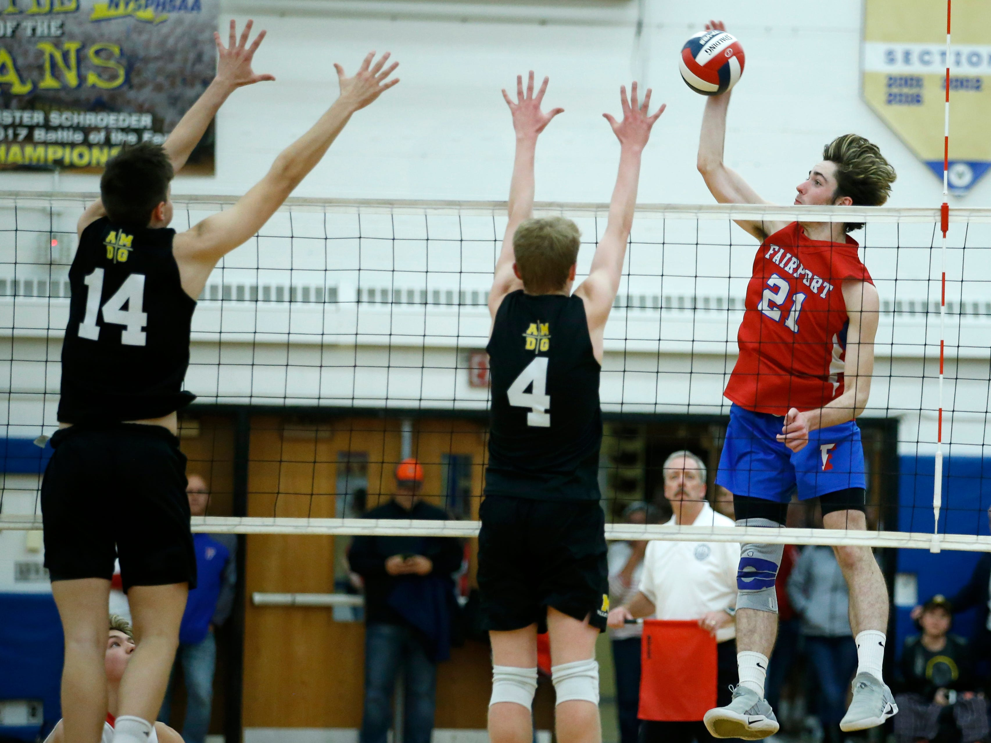 Class A volleyball final: Fairport's Matt Beiter faces a block by McQuaid's Daniel Lynch and Owen Wickens in the second set at Webster Schroeder High School.