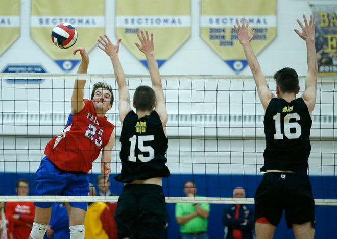 Class A volleyball final: Fairport's Ryan Parker attacks gets the ball past McQuaid's Keeler Thomas in the third set at Webster Schroeder High School.