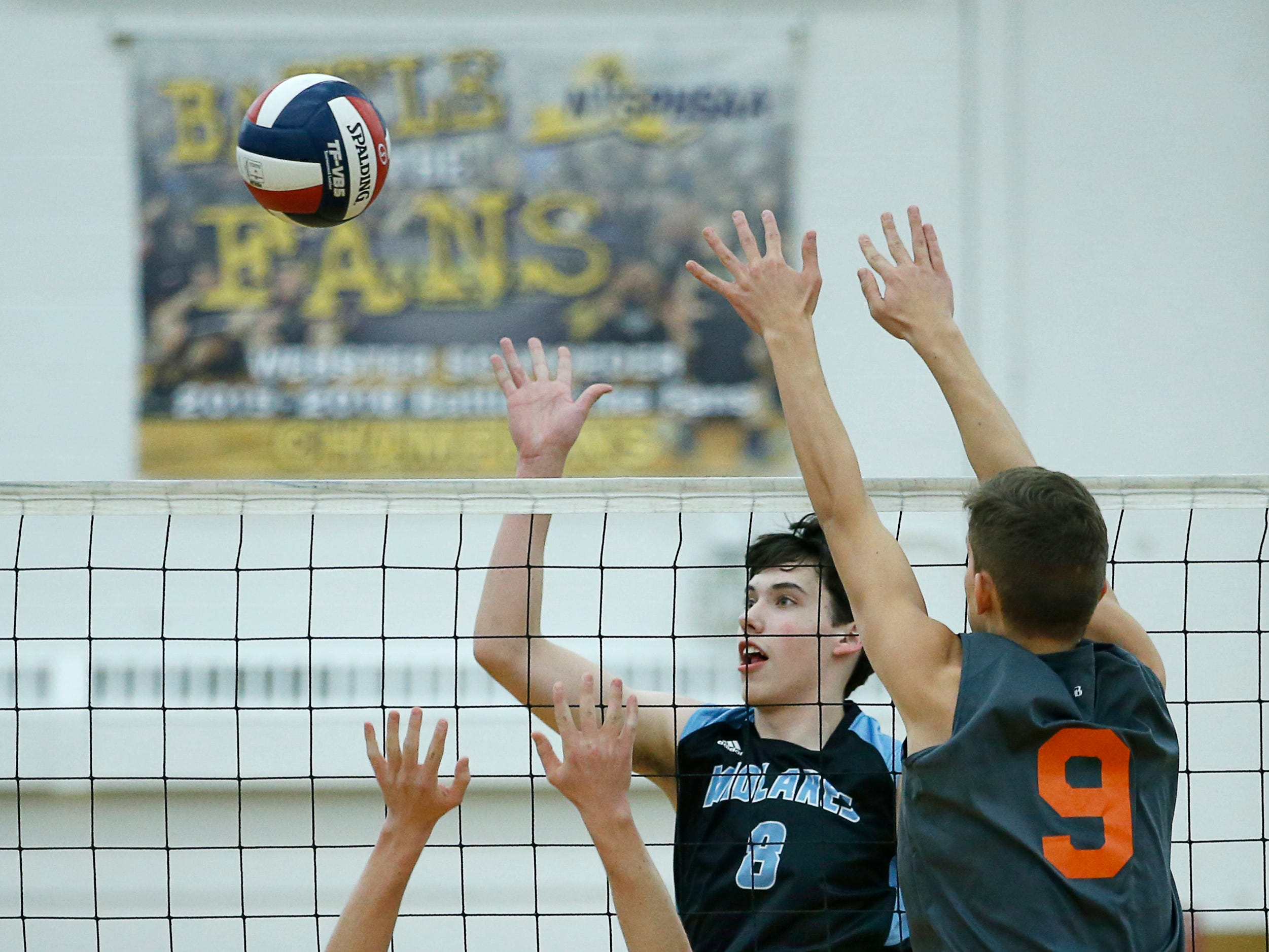 Class B volleyball final: Midlakes' Kyle McCann taps the ball over Churchville-Chili's John Keele and Greg Czolgosz in the first set at Webster Schroeder High School.