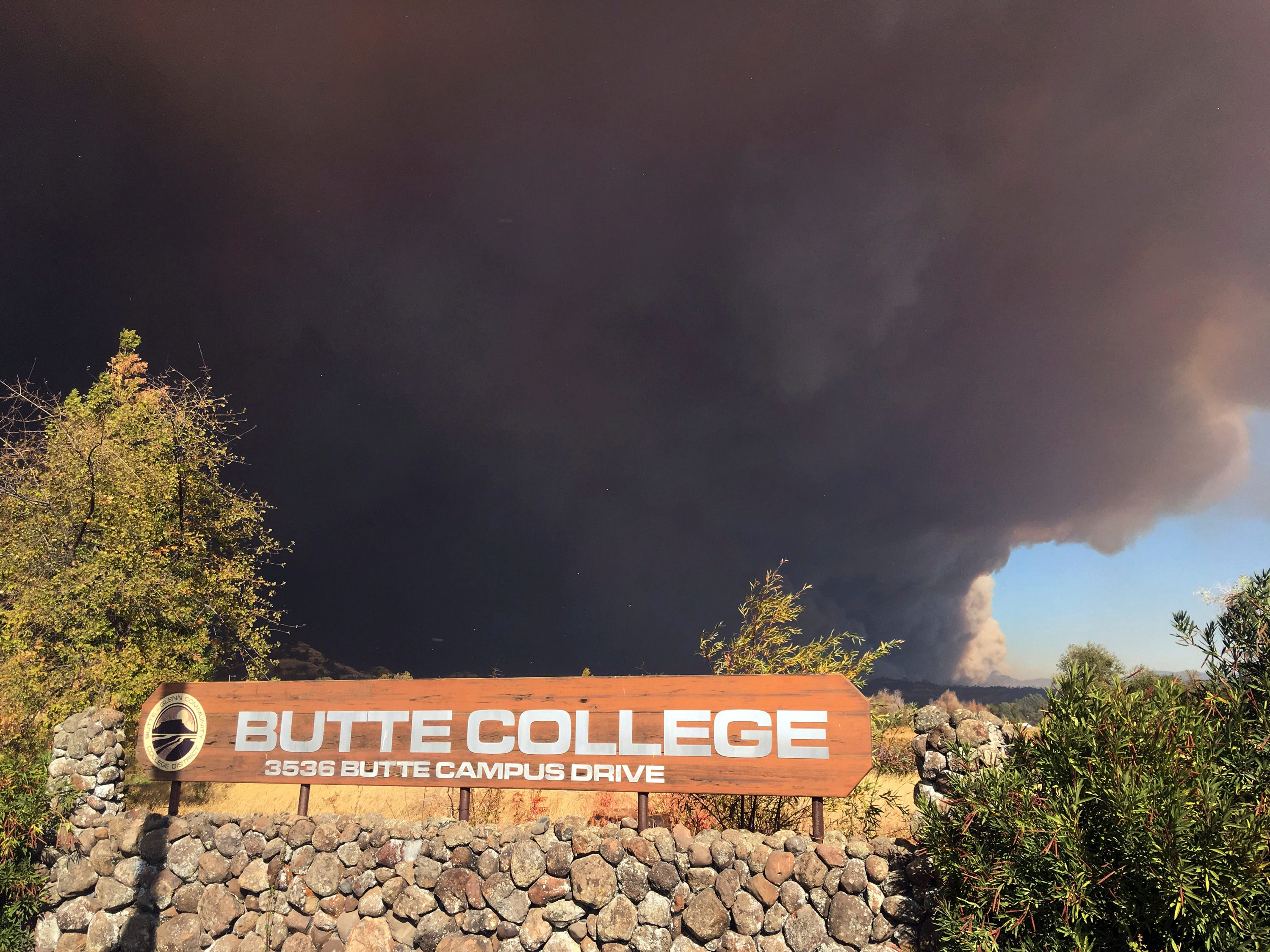 Smoke from the Camp Fire, burning in the Feather River Canyon near Paradise, Calif., darkens the sky above the Butte College sig in Oroville, Calif., Thursday, Nov. 8, 2018.
