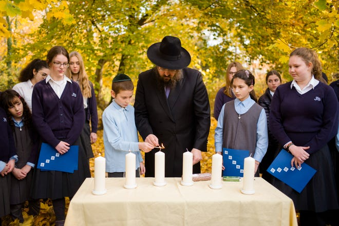 Rabbi Yehuda Teichtal, center, light candles with students during an event to commemorate the victims of the Nov. 9, 1938 terror against the Jews in Germany at the Jewish Traditional School in Berlin, Wednesday, Nov. 7, 2018.