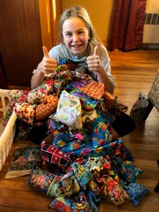Makenah Cowles poses for a photo with her hand-made Peace Packs.