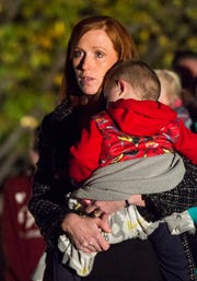 Jennie Taylor, holds her 2-year-old son Jonathan, as she says a few words during a candlelight vigil, Wednesday, Nov. 7, 2018, in front of her home in North Ogden for her husband Brent Taylor, was killed Saturday in an insider attack in Kabul, Afghanistan. (Rick Egan/The Salt Lake Tribune via AP)