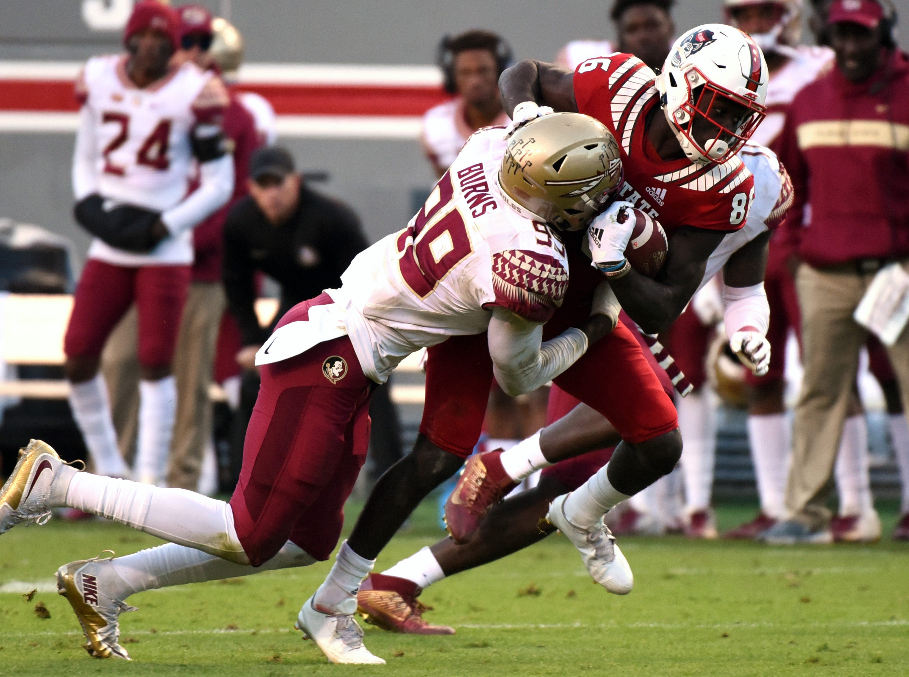 Nov 3, 2018; Raleigh, NC, USA; North Carolina State Wolfpack wide receiver Emeka Emizie (86) is tackled after a catch by Florida State Seminoles defensive end Brian Burns (99) during the second half at Carter-Finley Stadium.  The Wolfpack won 47-28.  Mandatory Credit: Rob Kinnan-USA TODAY Sports