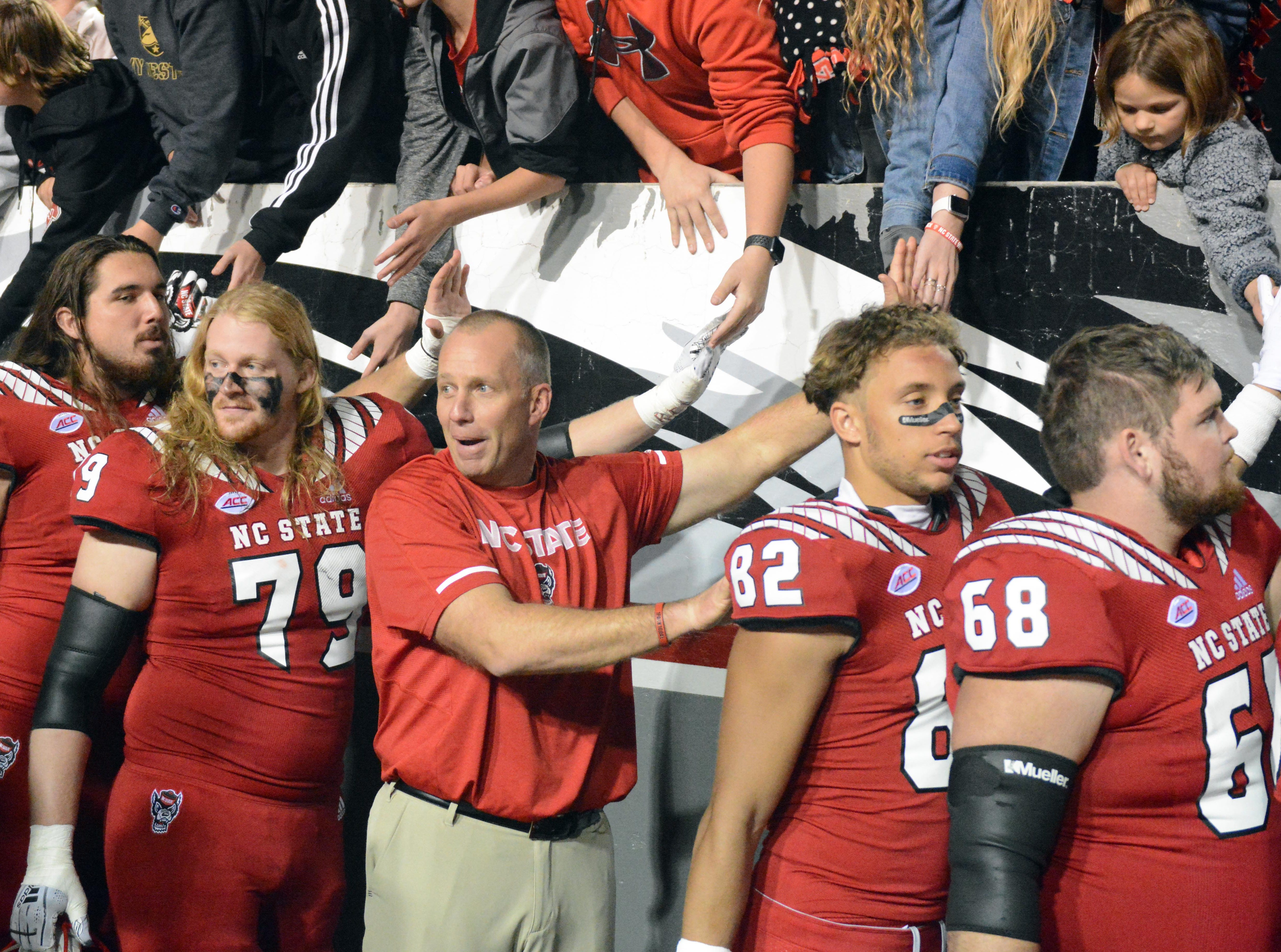 Nov 3, 2018; Raleigh, NC, USA; North Carolina State Wolfpack head coach Dave Doeren (center) greets fans after a victory against the Florida State Seminoles at Carter-Finley Stadium.  The Wolfpack won 47-28.  Mandatory Credit: Rob Kinnan-USA TODAY Sports