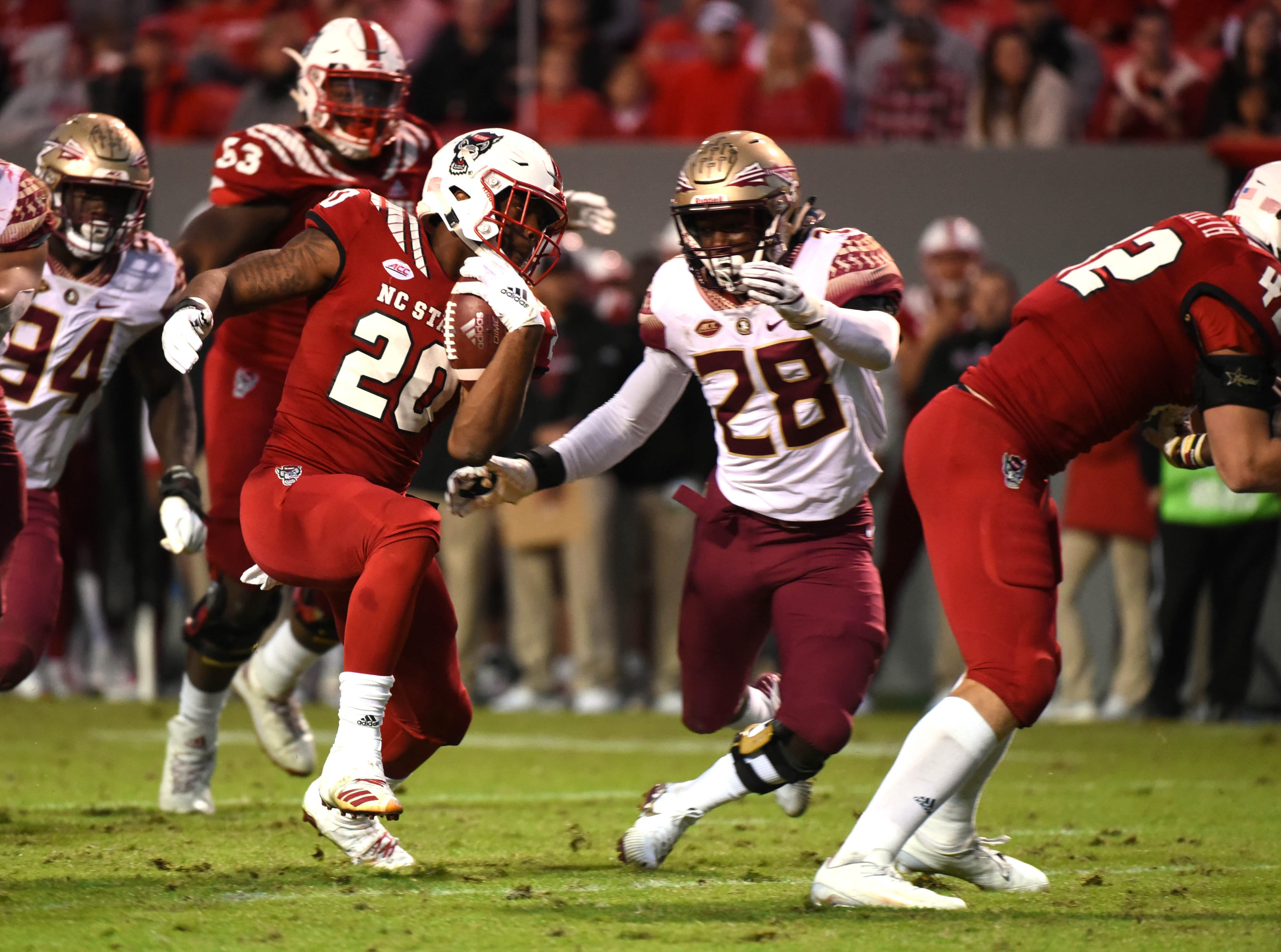 Nov 3, 2018; Raleigh, NC, USA; North Carolina State Wolfpack running back Ricky Person Jr. (20) eludes Florida State Seminoles linebacker DeCalon Brooks (28) during the second half at Carter-Finley Stadium.  The Wolfpack won 47-28.  Mandatory Credit: Rob Kinnan-USA TODAY Sports