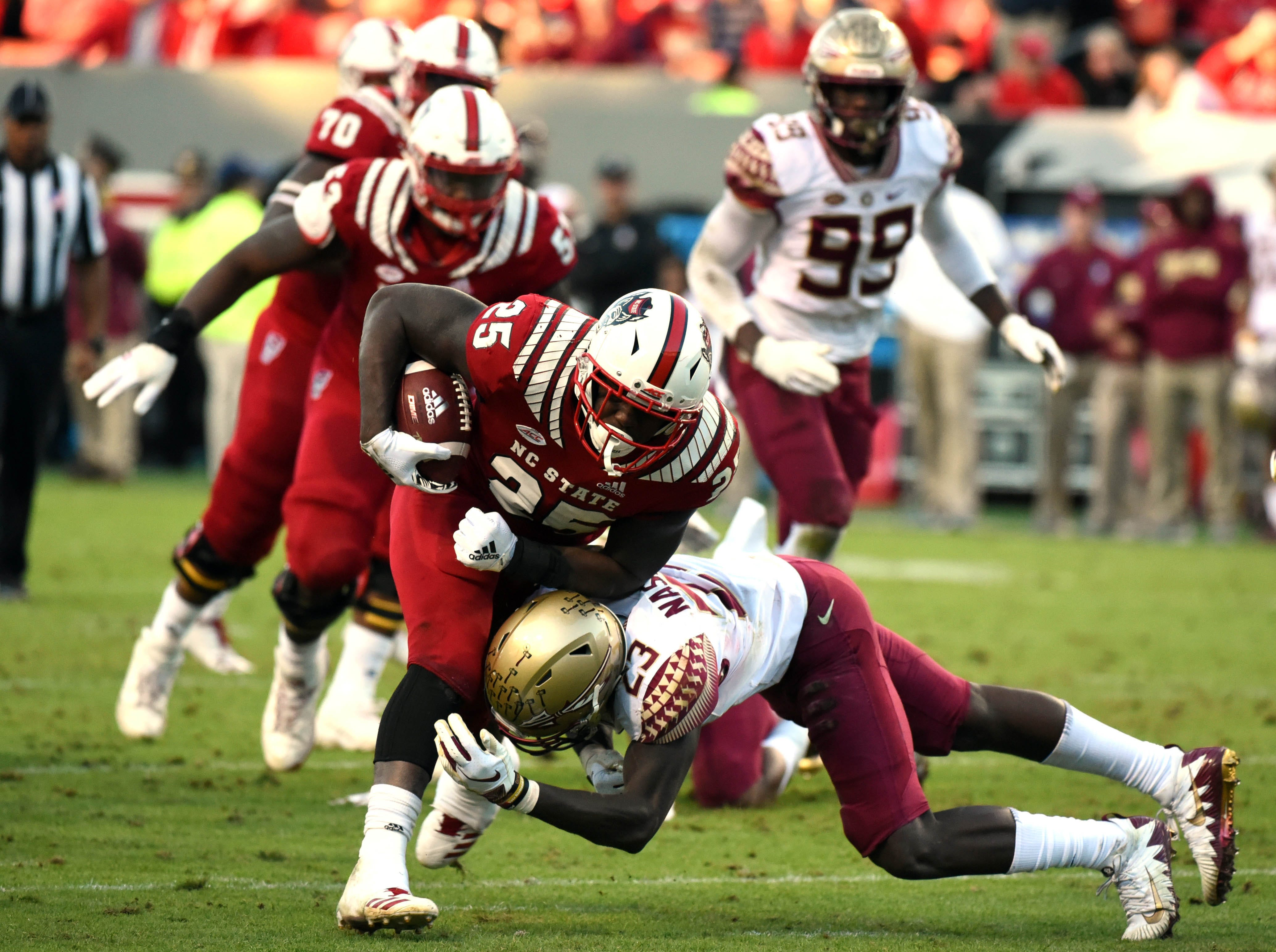 Nov 3, 2018; Raleigh, NC, USA; North Carolina State Wolfpack running back Reggie Gallaspy Jr. (25) is tackled by Florida State Seminoles defensive back Hamsah Masirildeen (23) during the second half at Carter-Finley Stadium.  The Wolfpack won 47-28.  Mandatory Credit: Rob Kinnan-USA TODAY Sports