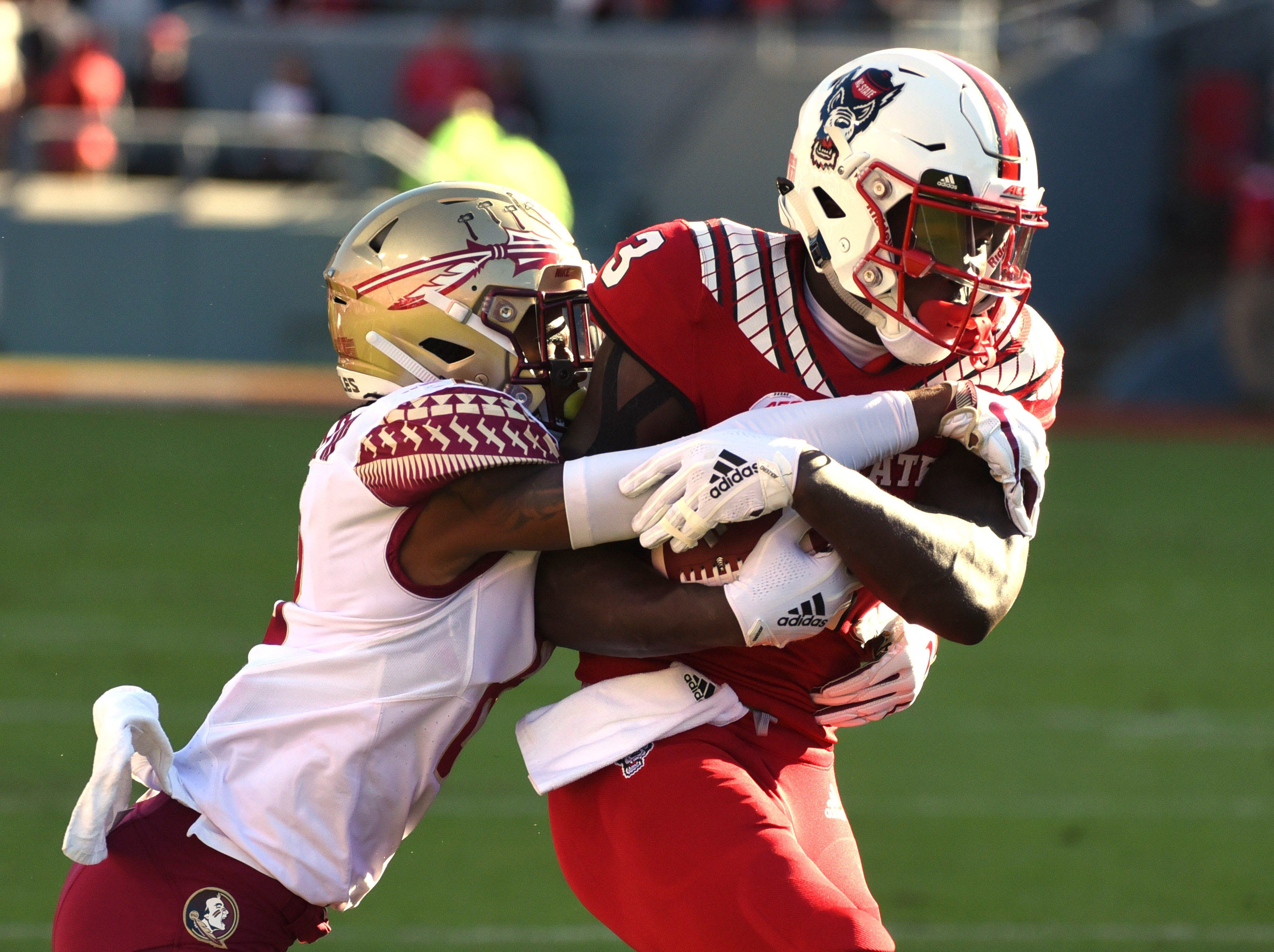 Nov 3, 2018; Raleigh, NC, USA; North Carolina State Wolfpack wide receiver Kelvin Harmon (3) is tackled after a catch by Florida State Seminoles defensive back Stanford Samuels III (8) during the first half at Carter-Finley Stadium. Mandatory Credit: Rob Kinnan-USA TODAY Sports