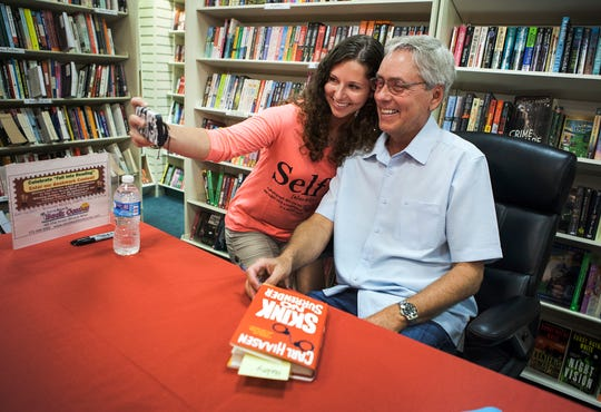 Carl Hiaasen, best-selling author from Vero Beach, takes a selfie with fan, Haley Sanders, 18, of Melbourne, while signing copies of his new book, Skink No Surrender, after speaking to a standing room only audience Oct. 3, 2014, at the event at the Vero Beach Book Center.