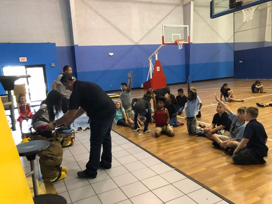 Children at the Boys & Girls Club of Hobe Sound tried on bunker gear as a part of Fire Education Day.