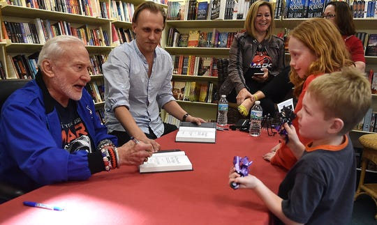 "Buzz Aldrin (left), Apollo 11 astronaut and the second man to walk on the moon, talks with Bryce Kane, 9, (second from right) and her brother Brenner, 5, both of Westborough Massachusetts, while signing books at the Vero Beach Book Center on Tuesday, April 19, 2016, in Vero Beach. ""I never met a real astronaut before,"" Brenner said."