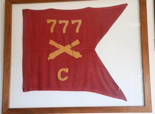 A guidon from the first artillery unit Edward Greer served with in World War II decorates his military room.