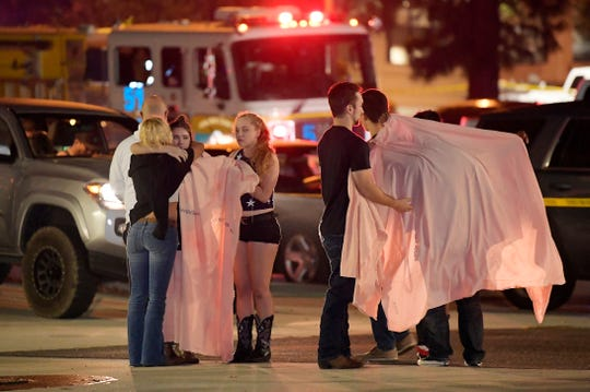 People comfort each other as they stand near the scene after a mass shooting at the Borderline Bar & Grill in Thousand Oaks.
