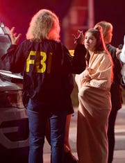 An FBI agent talks to a potential witness as they stand near the scene Thursday  after a mass shooting at the Borderline Bar & Grill in Thousand Oaks.