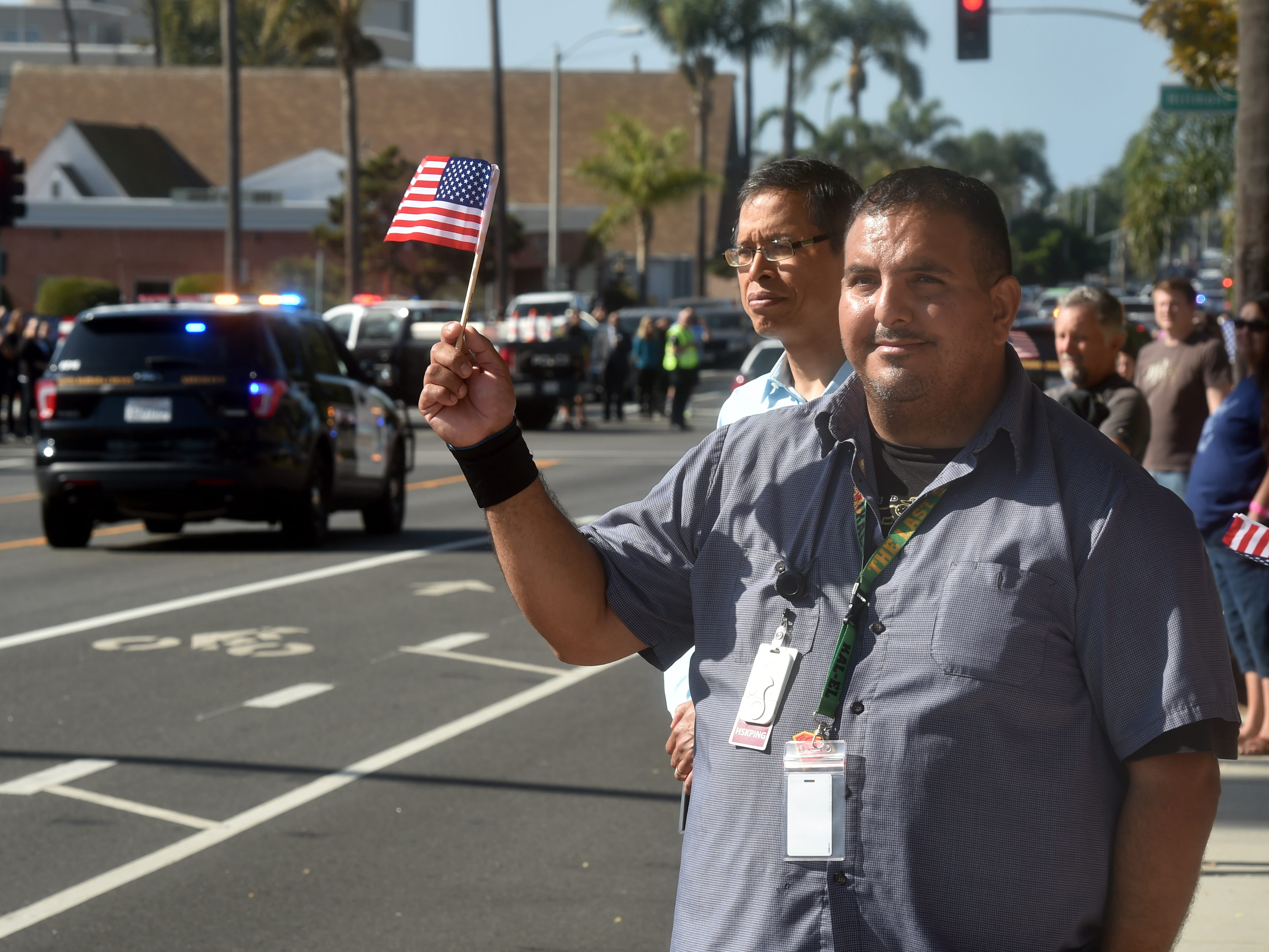 Josue Lara, a janitor at Ventura County Medical Center, watches along Loma Vista Road as a procession passes by carrying the body of Ventura County Sheriff Sgt. Ron Helus, who was one of 12 victims of the shooting in Thousand Oaks late Wednesday.