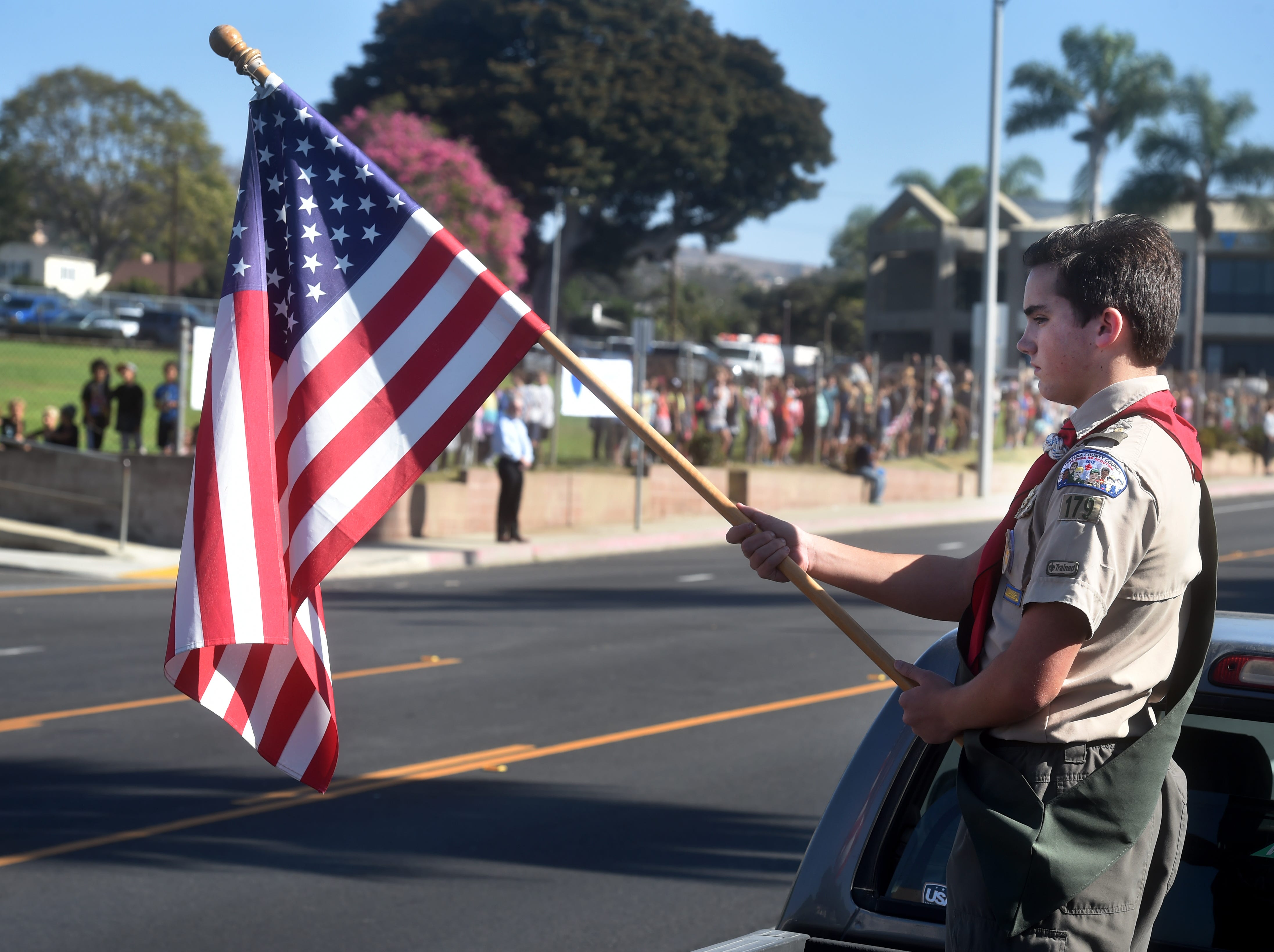 Grant Dullam, 15, of Ventura, holds up a flag across from Loma Vista Elementary as hundreds wait along Loma Vista Road for a procession carrying the body of Ventura County Sheriff Sgt. Ron Helus, who was one of 12 victims of the shooting in Thousand Oaks late Wednesday.