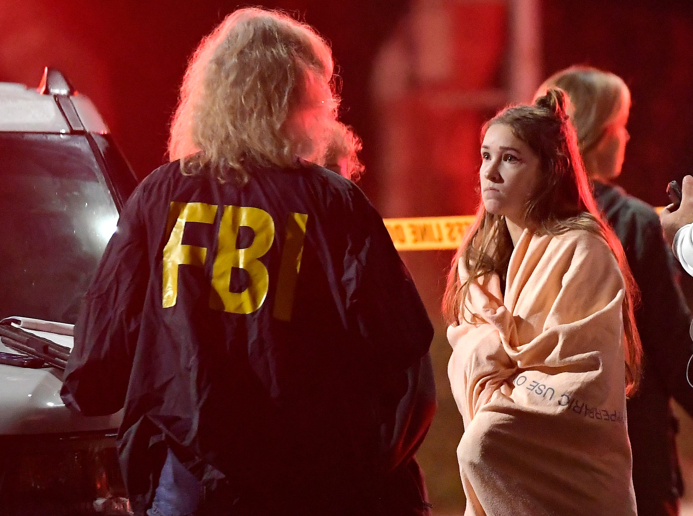 An FBI agent talks to a potential witness as they stand near the scene  after a mass shooting at the Borderline Bar & Grill in Thousand Oaks.
