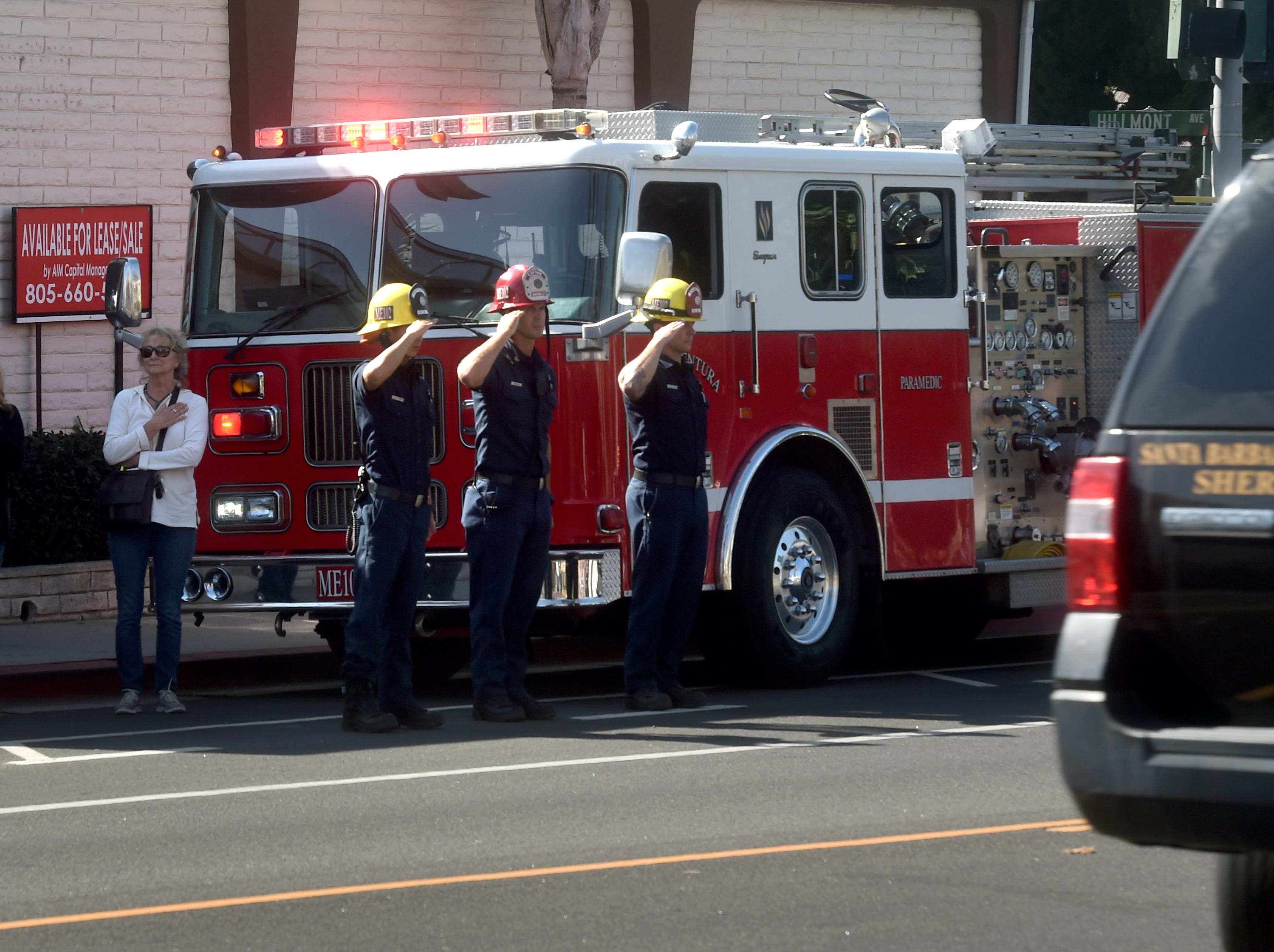 Firefighters salute in front of Ventura County Medical Center on Thursday as a procession passes by carrying the body of Ventura County Sheriff Sgt. Ron Helus, who was one of 12 victims of the shooting in Thousand Oaks late Wednesday.