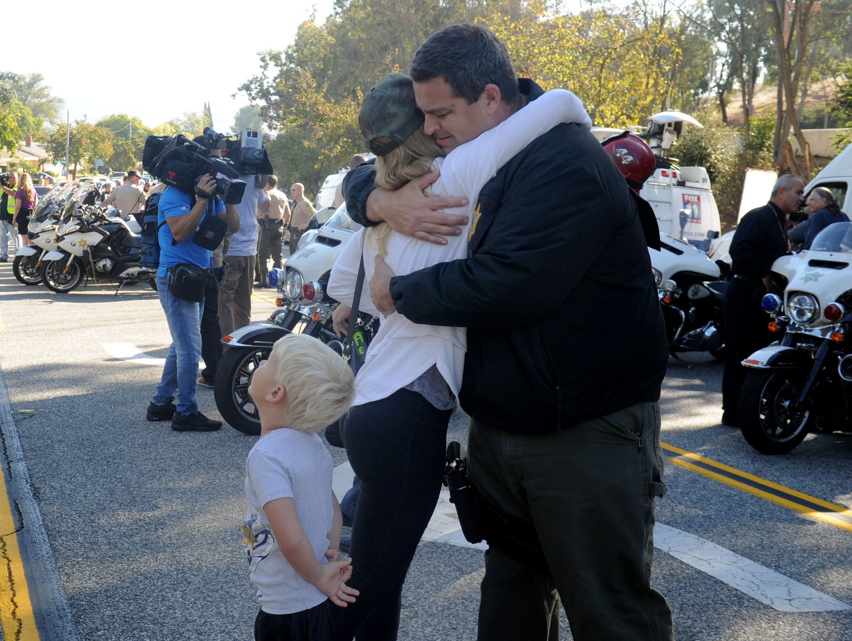 Sarah Sauer and her son Paul Sauer, 4, hug Chris Dyer, sheriff deputy at the  procession of Sgt. Ron Helus' body from Los Robles Regional Medical Center  to Ventura Thursday morning.