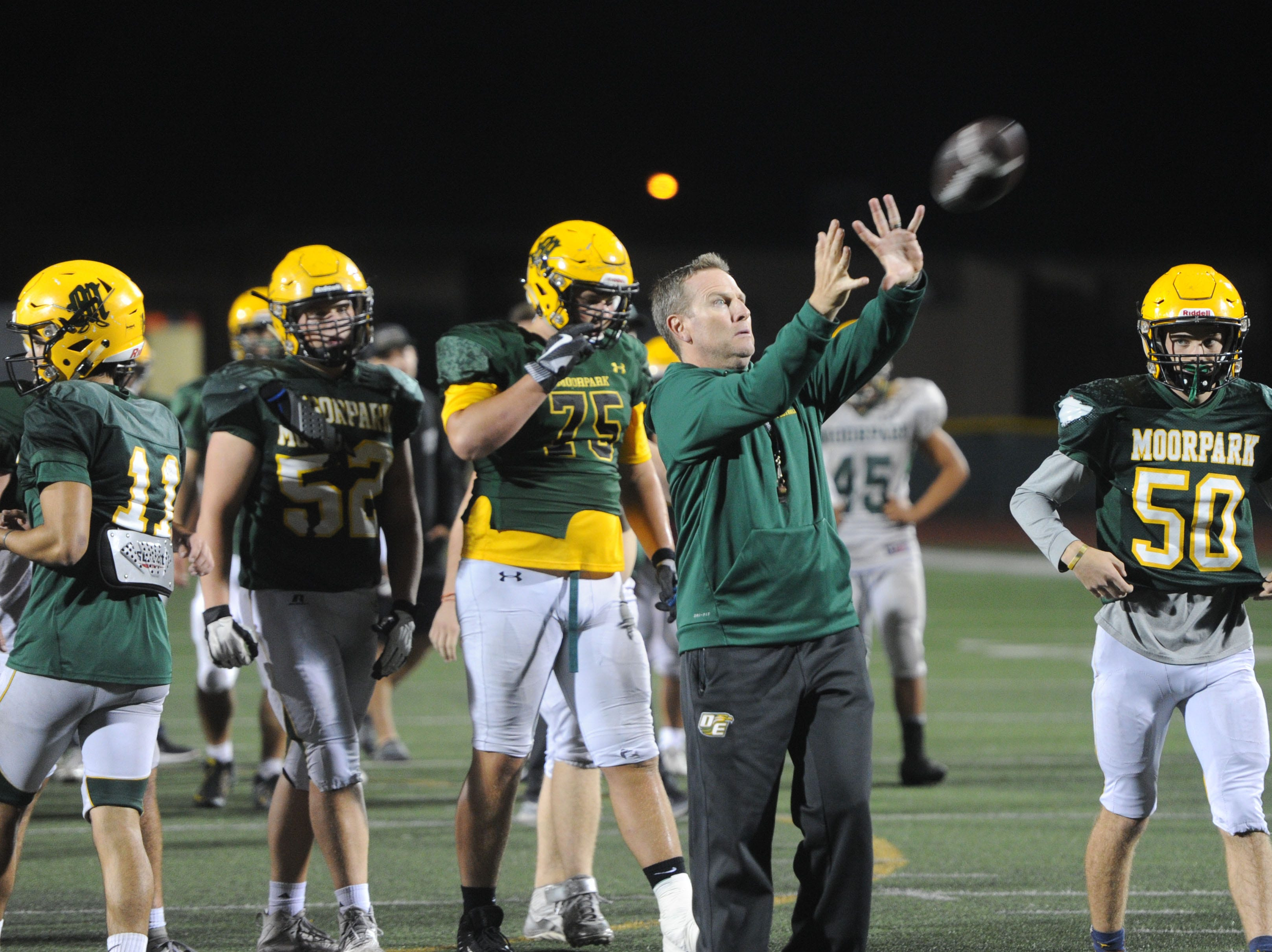 Head coach Ryan Huisenga catches the ball during Moorpark's practice Wednesday. The Musketeers host Sierra Canyon in a Division 3 quarterfinal game Friday night.