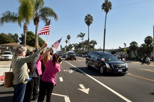 A hearse carrying the body of Ventura County Sheriff Sgt. Ron Helus, who was one of 12 victims of the shooting in Thousand Oaks late Wednesday, passes hundreds of supporters along Loma Vista Road on its way to the Ventura County Medical Examiners office on Thursday.