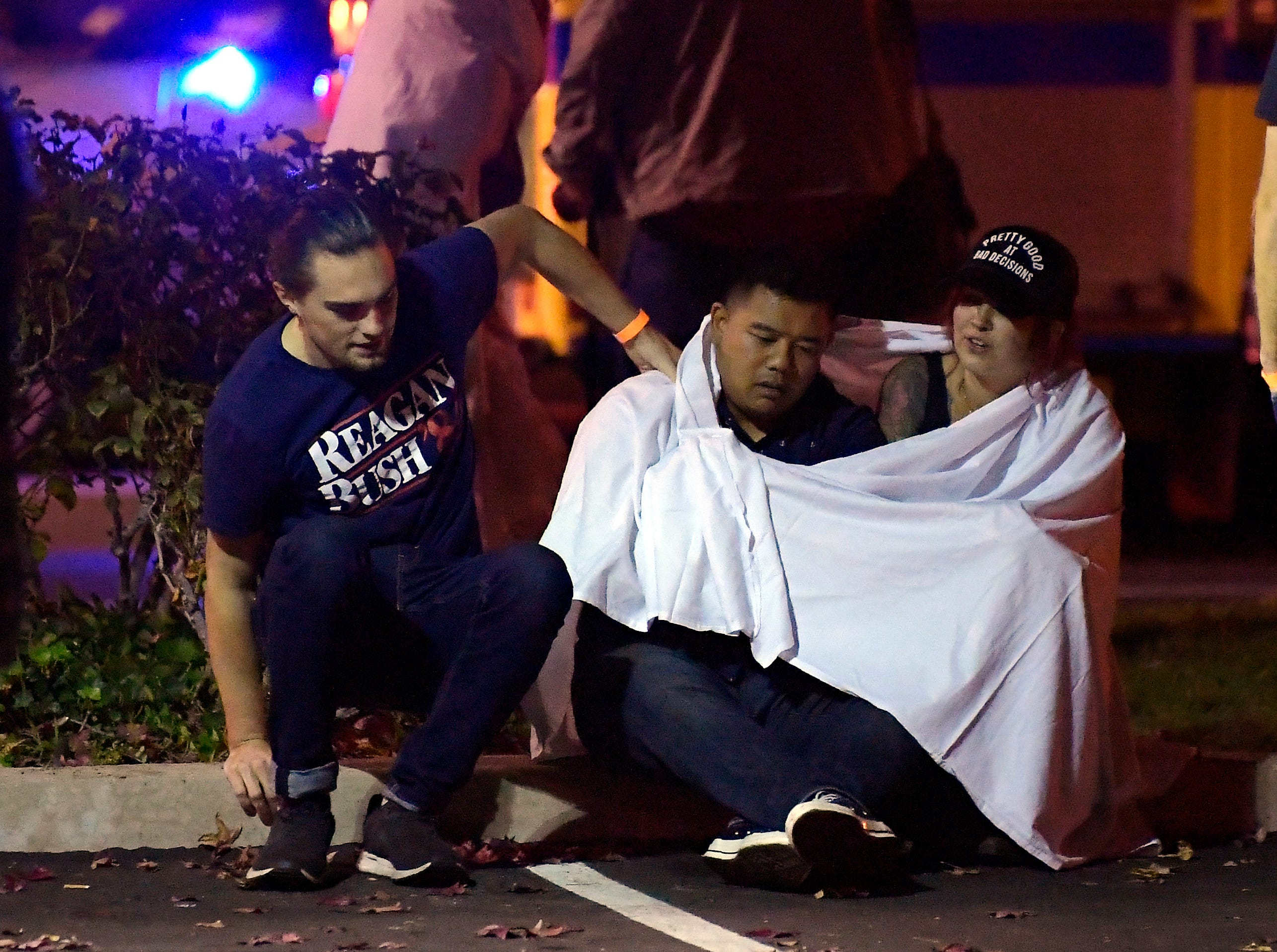 People comfort each other as they sit near the scene Thursday in Thousand Oaks where a gunman opened fire Wednesday inside the Borderline Bar & Grill that was crowded with hundreds of people.