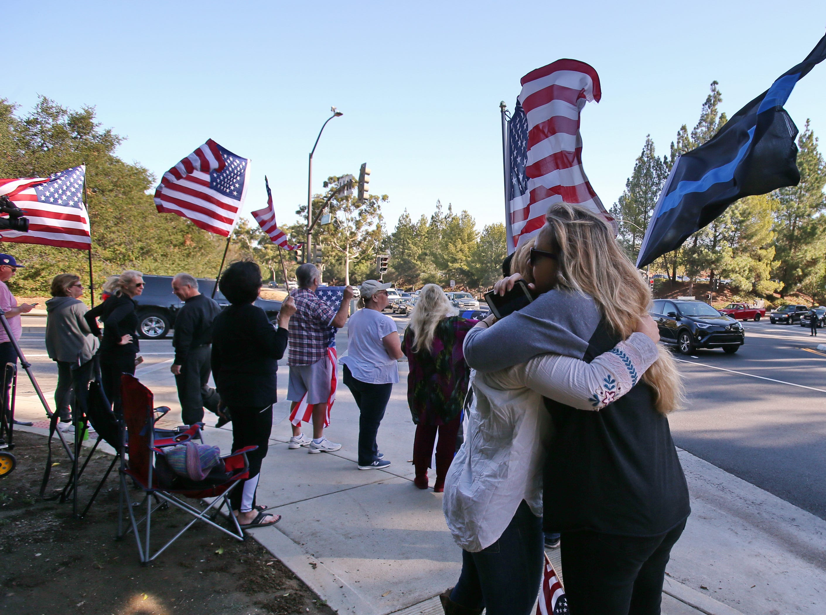 Deanna Ochoa (right) and Jennifer Smith greets each other with a hug as they wait for the procession for Ventura County Sheriff Sgt. Ron Helus to start Thursday. Helus was killed inside the Borderline Bar and Grill in Thousand Oaks late Wednesday, when 13 people died including the gunman in a mass shooting.