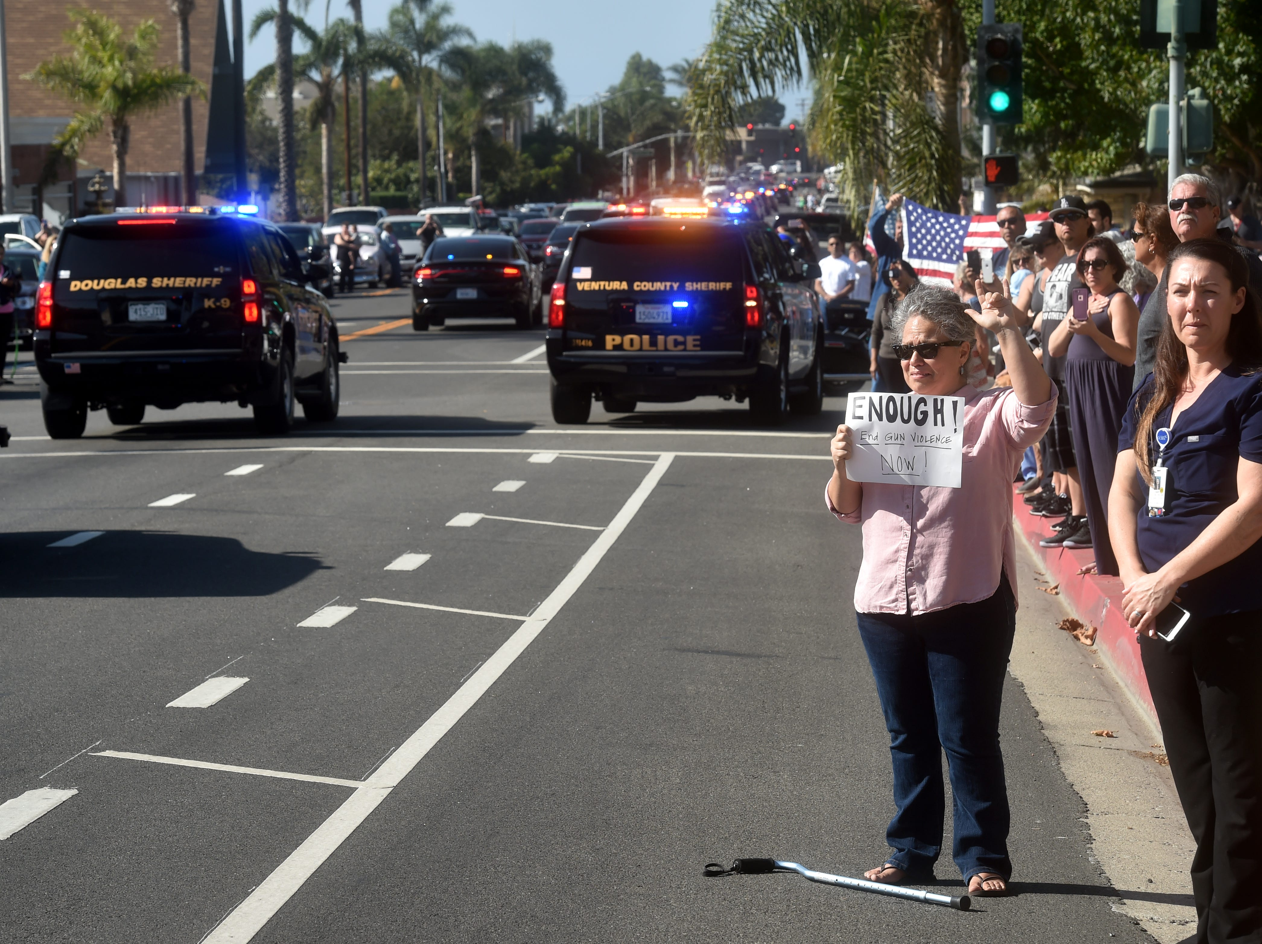 Mary Perry, of Ventura, cries while she holds a sign advocating for gu control as a procession passes by carrying the body of Ventura County Sheriff Sgt. Ron Helus passes by on Thursday. Helus was one of 12 victims of a shooting in Thousand Oaks late Wednesday.