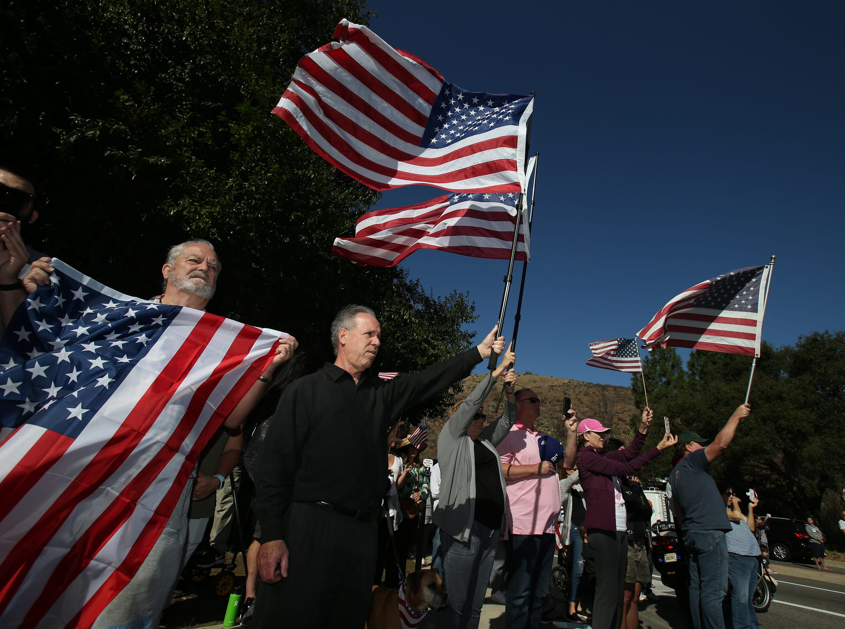 Eric Bosworth (center) waves his American flag as the procession for Ventura County Sheriff Sgt. Ron Helus passes by a gathering at Lynn and Janss Roads in Thousand Oaks on Thursday. Helus was killed inside the Borderline Bar and Grill in Thousand Oaks late Wednesday, when 13 people died including the gunman in a mass shooting.