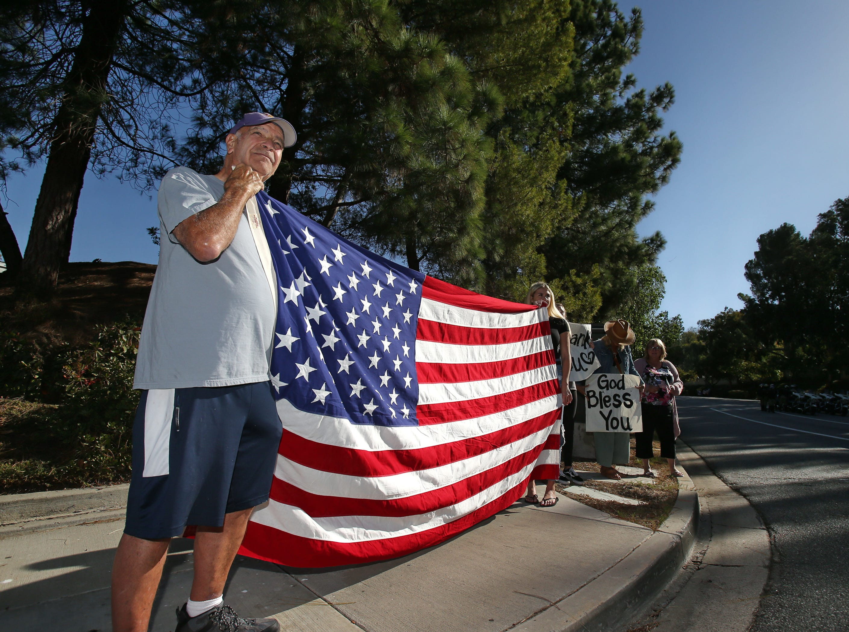 Richard Cook and his granddaughter Chloe Daland hold up an American flag as they pay their respects to Ventura County Sheriff Sgt. Ron Helus before his body leaves Los Robles Hospital on Thursday. Helus was killed inside the Borderline Bar and Grill in Thousand Oaks late Wednesday, when 13 people died including the gunman in a mass shooting.