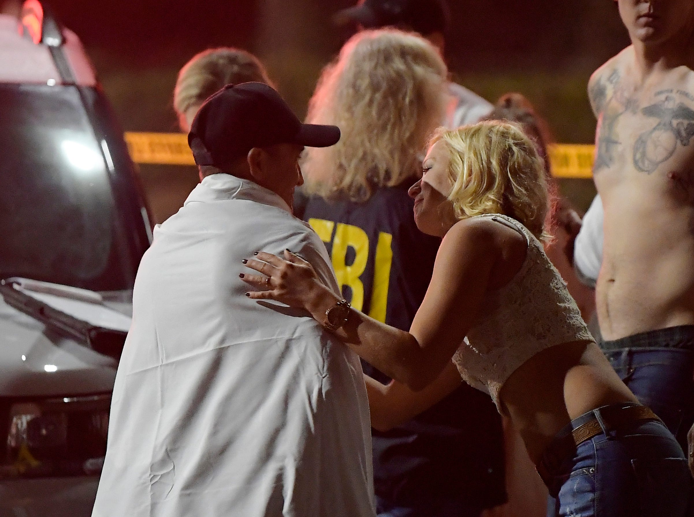 People comfort each other as they stand near the scene Thursday in Thousand Oaks  after a mass shooting at the Borderline Bar & Grill.