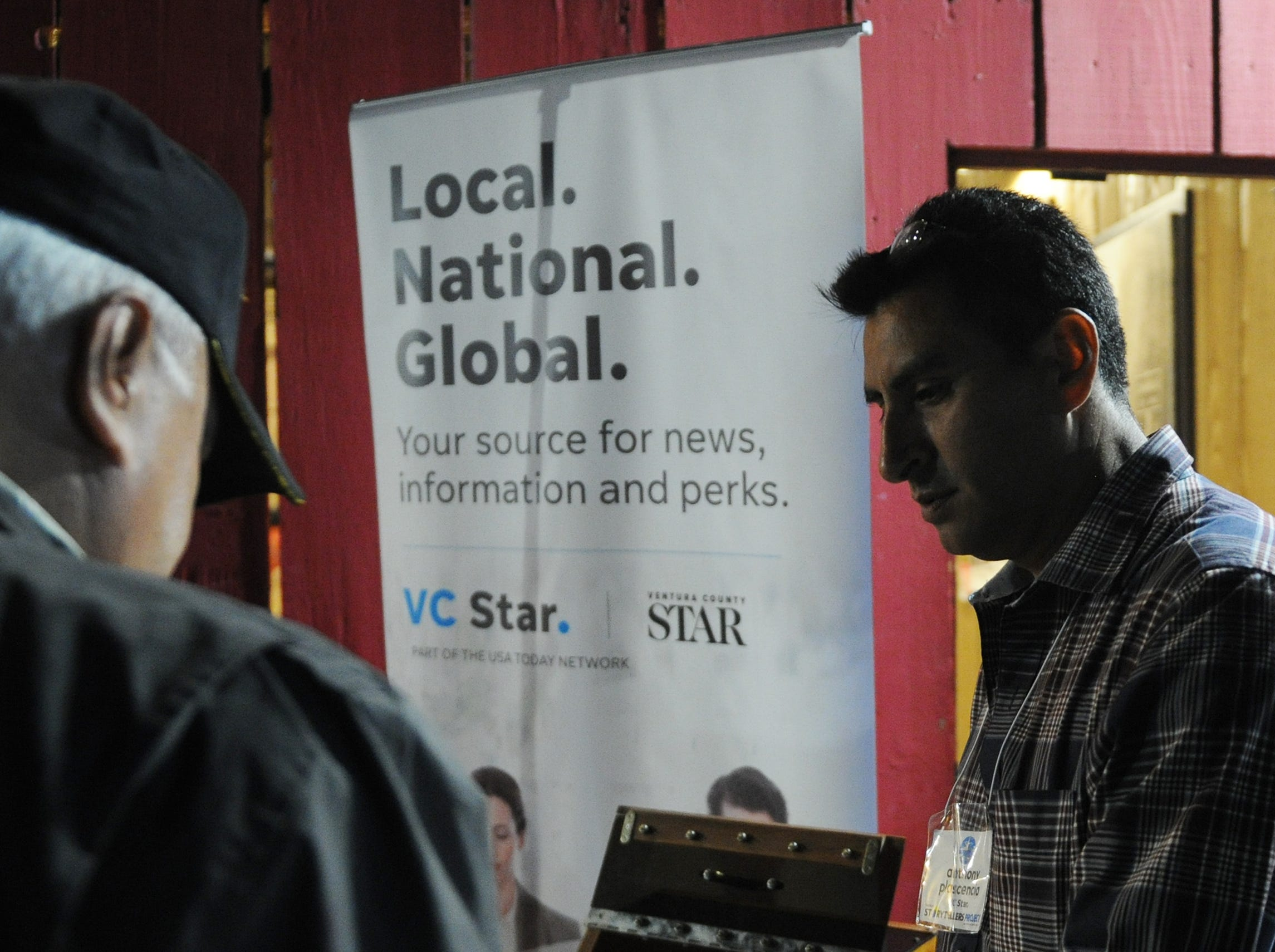 """Anthony Plascencia, right, staff photographer and videographer at the Ventura County Star, chats with those attending the Ventura Storytellers Project show, """"Holidays and Family,"""" at the Camarillo Ranch on Wednesday evening."""