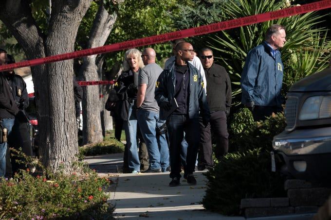 FBI investigators arrive outside the house of Ian David Long, the shooter in Wednesday's attack on the Borderline Bar & Grill in Thousand Oaks, as they wait to search the residence on Thursday in Newbury Park. Using a smoke bomb and a handgun, the former Marine opened fire during college night at the Borderline Bar & Grill, killing 12 people and sending hundreds fleeing in panic before apparently taking his own life, authorities said Thursday. Authorities said the motive for the attack was under investigation.