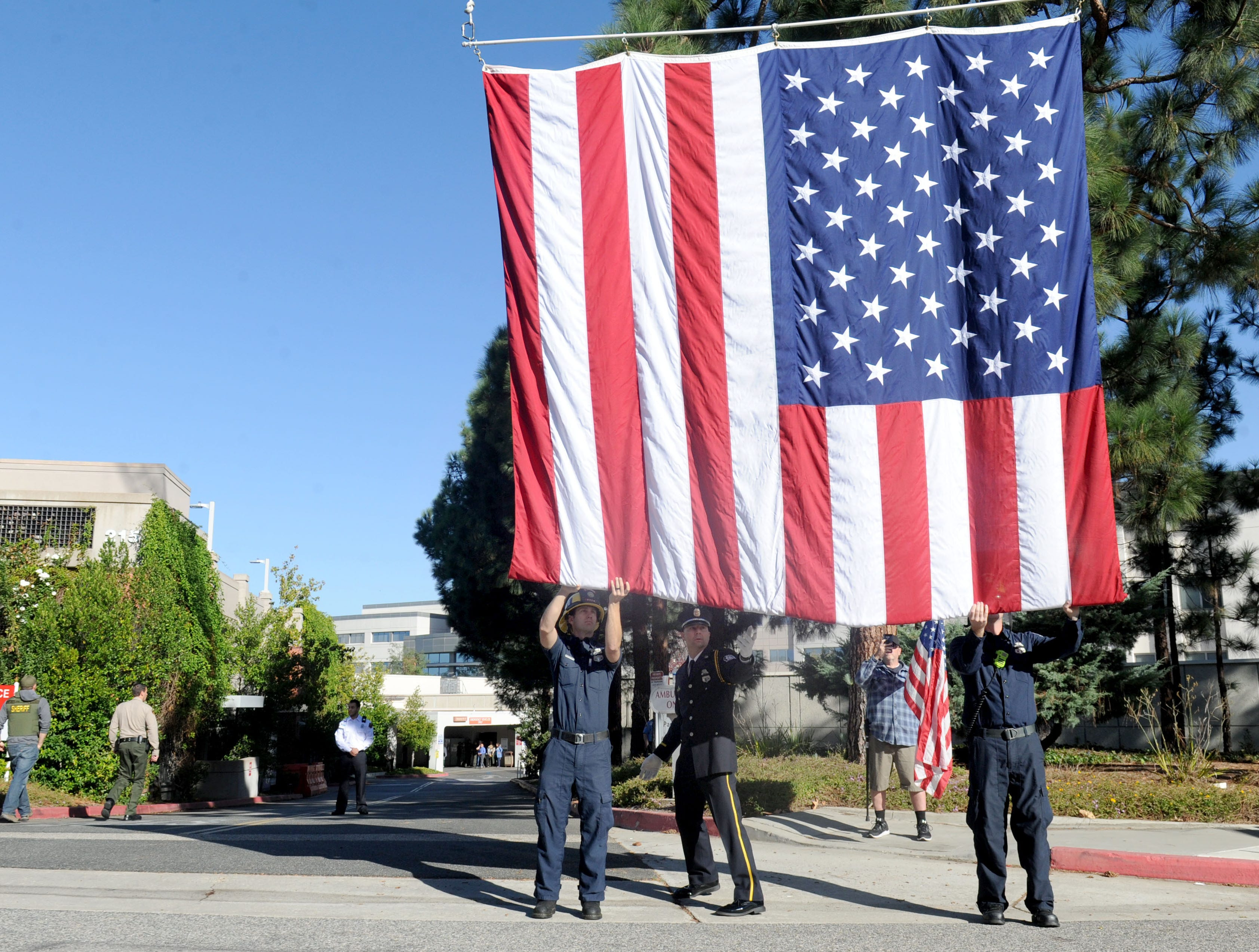 An American flag is raised at the procession of Sgt. Ron Helus' body at Los Robles Regional Medical Center Thursday morning. He was killed at the shooting at the Borderline Bar & Grill Wednesday night in Thousand Oaks.