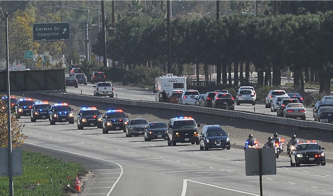 The procession for Ventura County Sheriff Sgt. Ron Helus travels Northbouhd on HIghway 101 at Las Posas Road in Camarillo. Helus was killed inside the Borderline Bar and Grill in Thousand Oaks, California, late Wednesday where 13 people died including the gunman in a mass shooting.