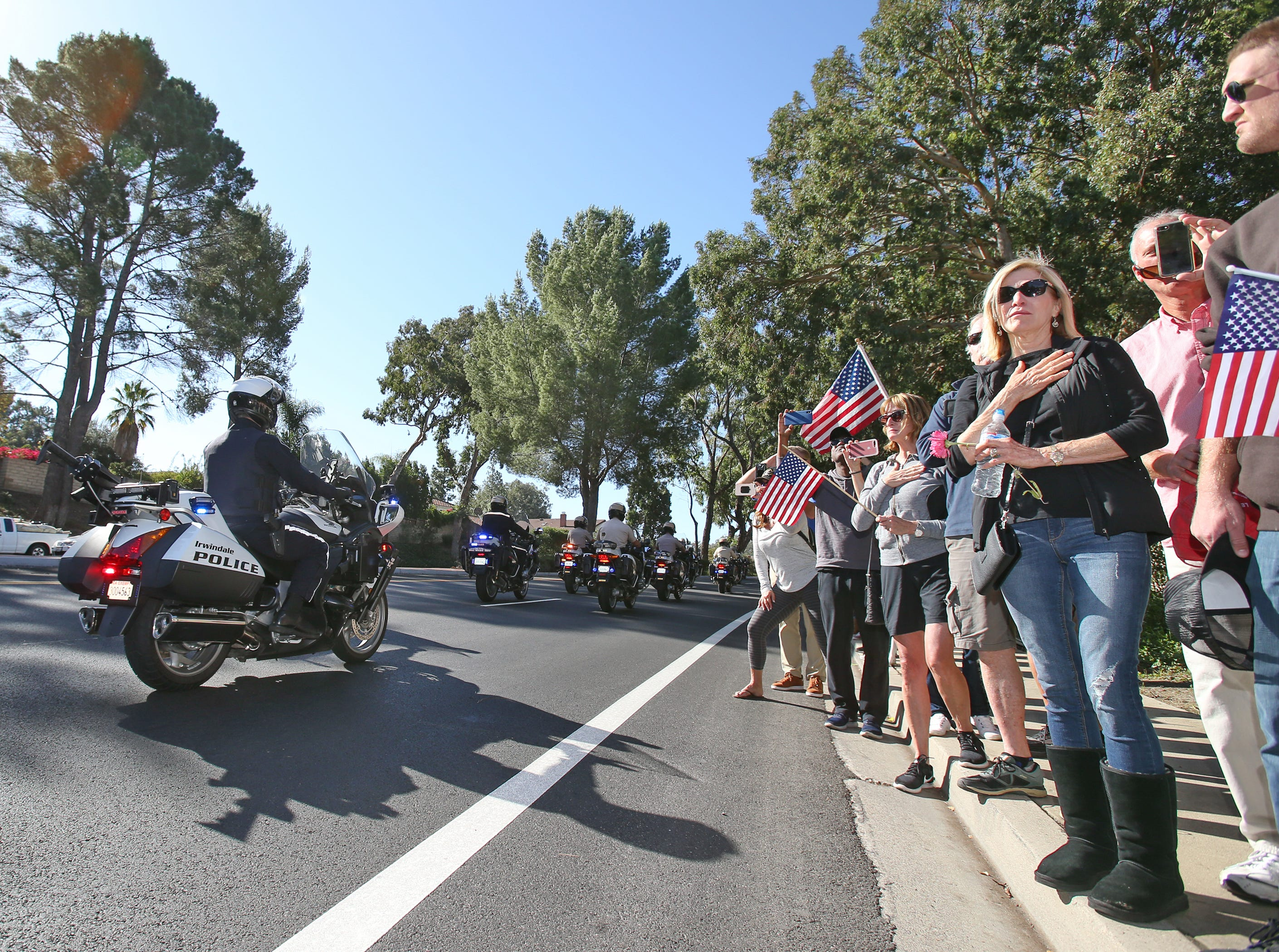 Members from the community pay their respects to Ventura County Sheriff Sgt. Ron Helus as procession leaves Los Robles Hospital in Thousand Oaks. Helus was killed inside the Borderline Bar and Grill in Thousand Oaks late Wednesday, when 13 people died including the gunman in a mass shooting.