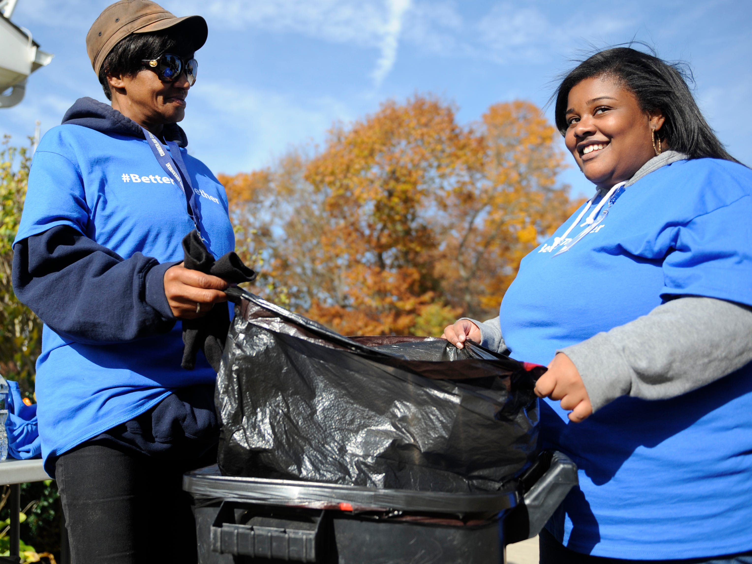 Angela Pernell (left) and Kai Dubrey help put away trash during a community clean up event at Oakview Apartments in Millville on Thursday, November 8, 2018.