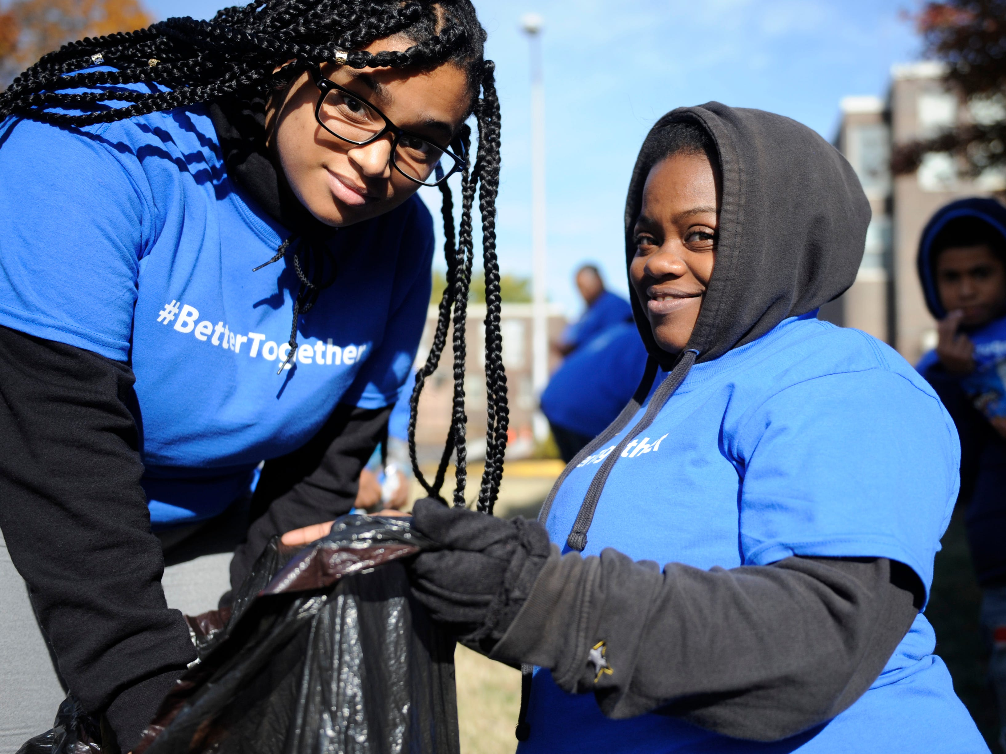Oakview Apartments neighbors Alexis Acosta, 16, (left) and Vernique Risley, 27, join in on the clean up festivities during a community event.