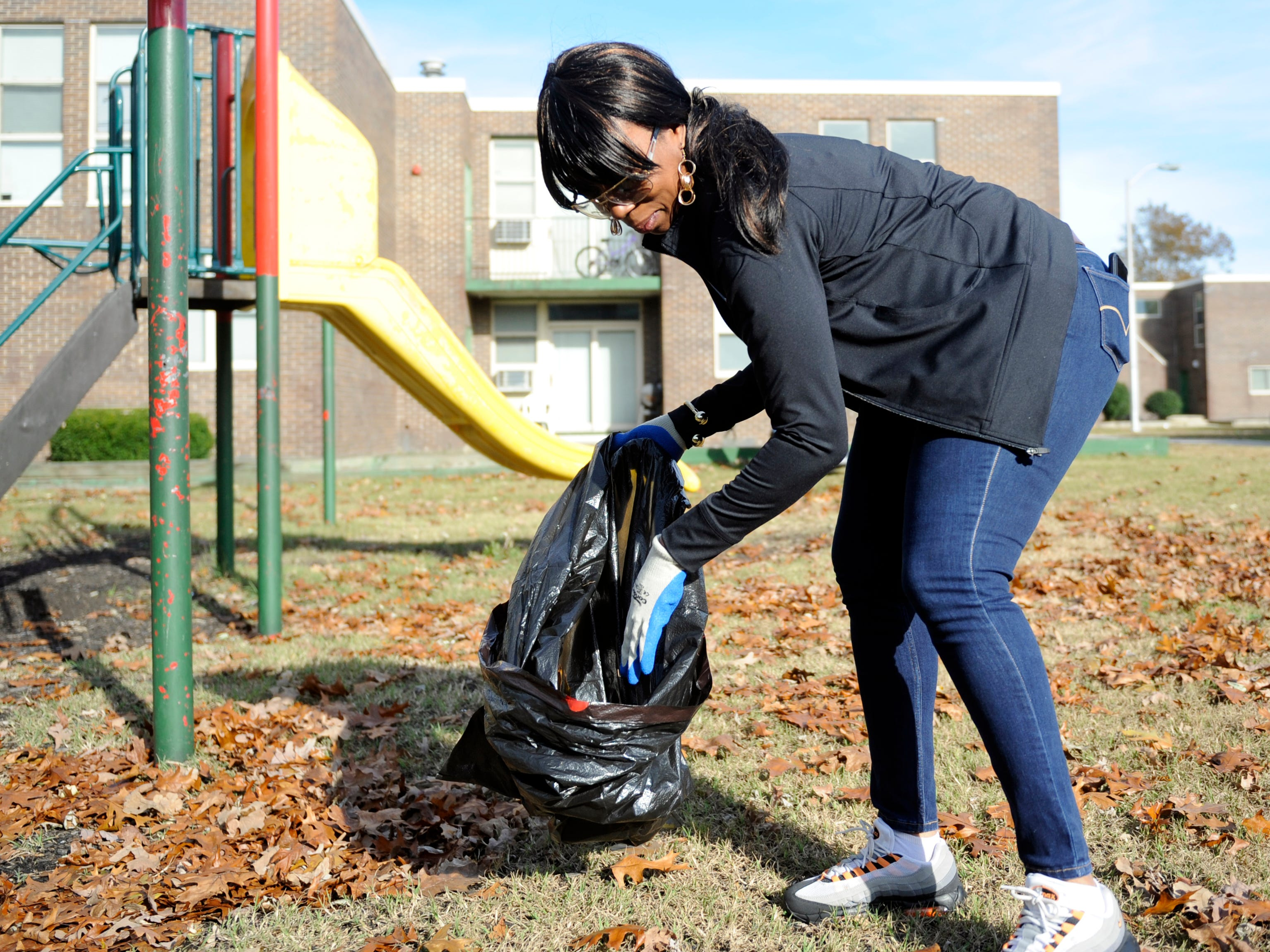 Jaclyn Garrett, Senior Property Manager at Oakview Apartments in Millville, picks up trash near a playground during a special community clean up event on Thursday, November 8, 2018.