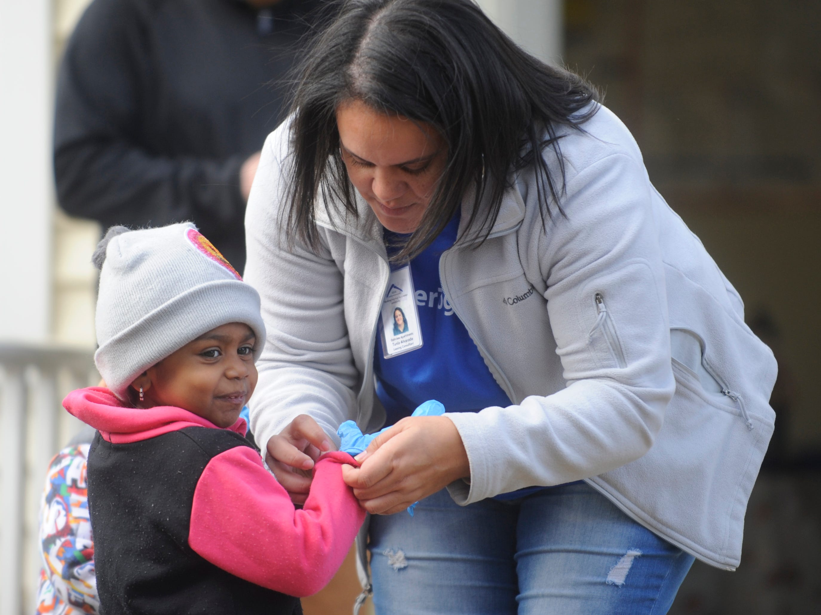 Tania Alvarado, leasing consultant at Oakview Apartments, helps a volunteer put on gloves for the facilities's community clean up event in Millville on Thursday, November 8, 2018.