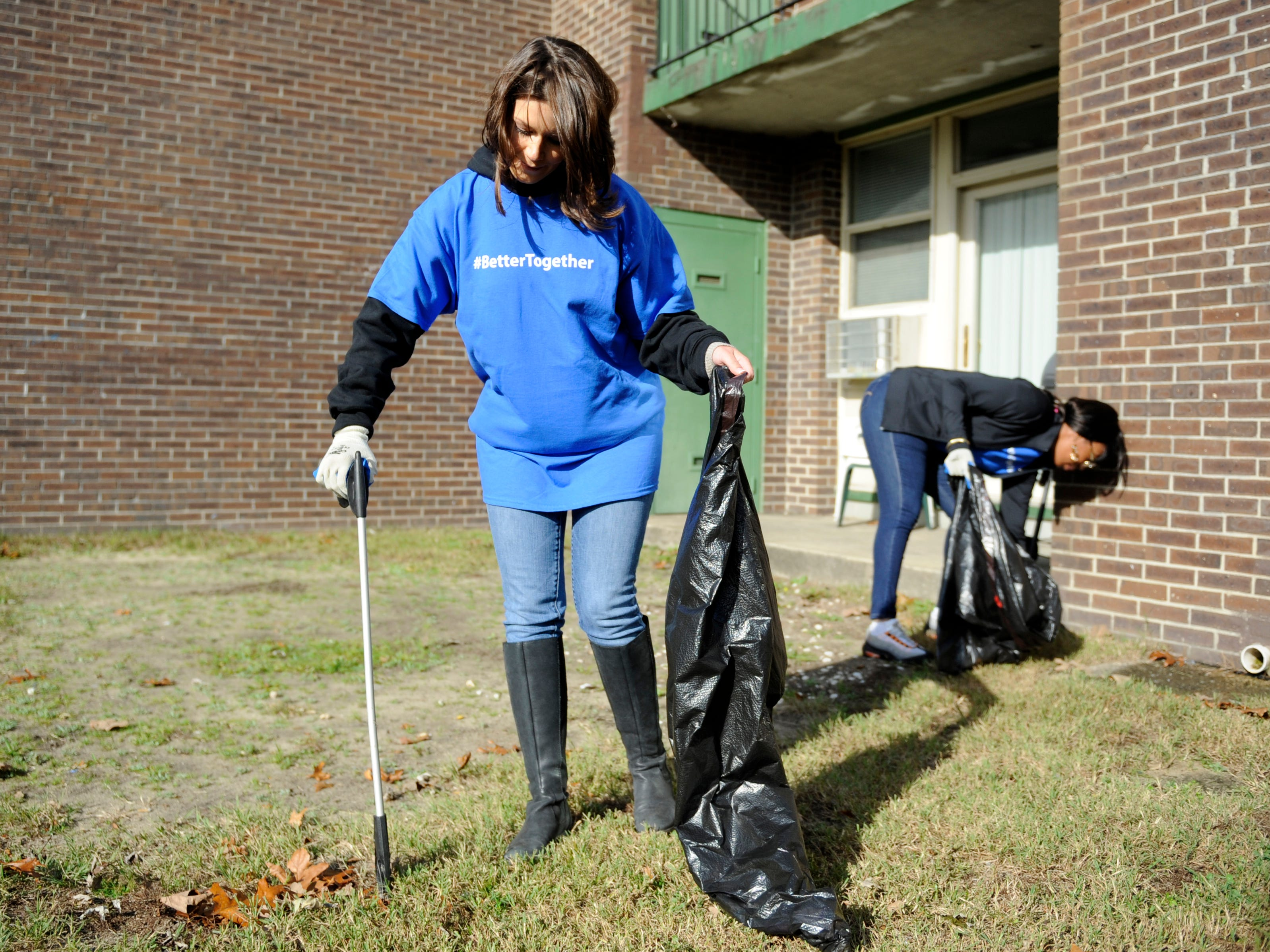 Ashleigh Udalovas, City of Millville Director of Public Affairs, helps clean up during a community event at Oakview Apartments.