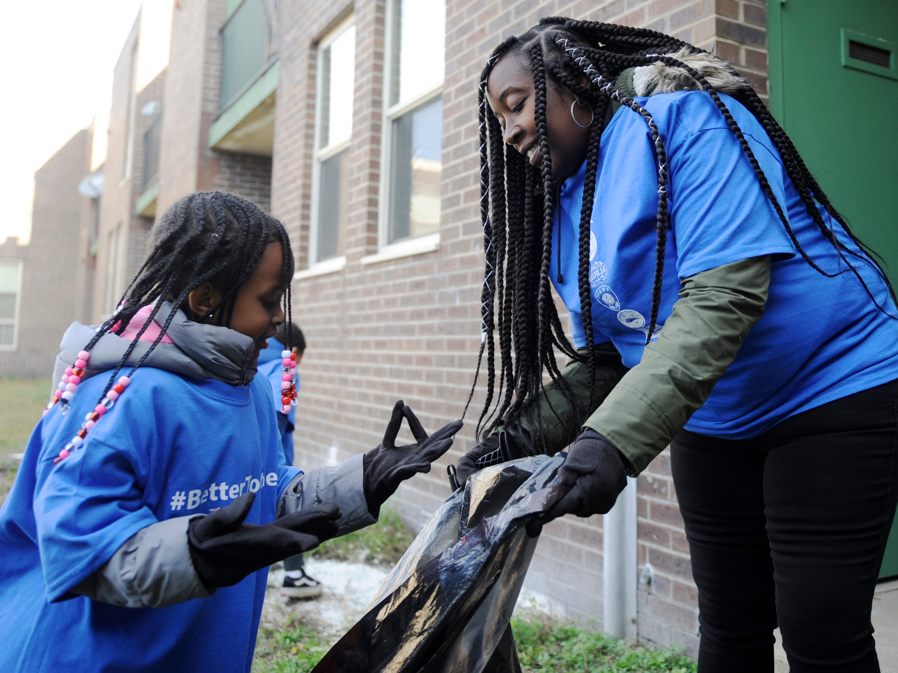• Oakview Apartments residents Dena Alsobrook (right) and daughter Saleya, 6, help with the  clean up efforts during a community event.