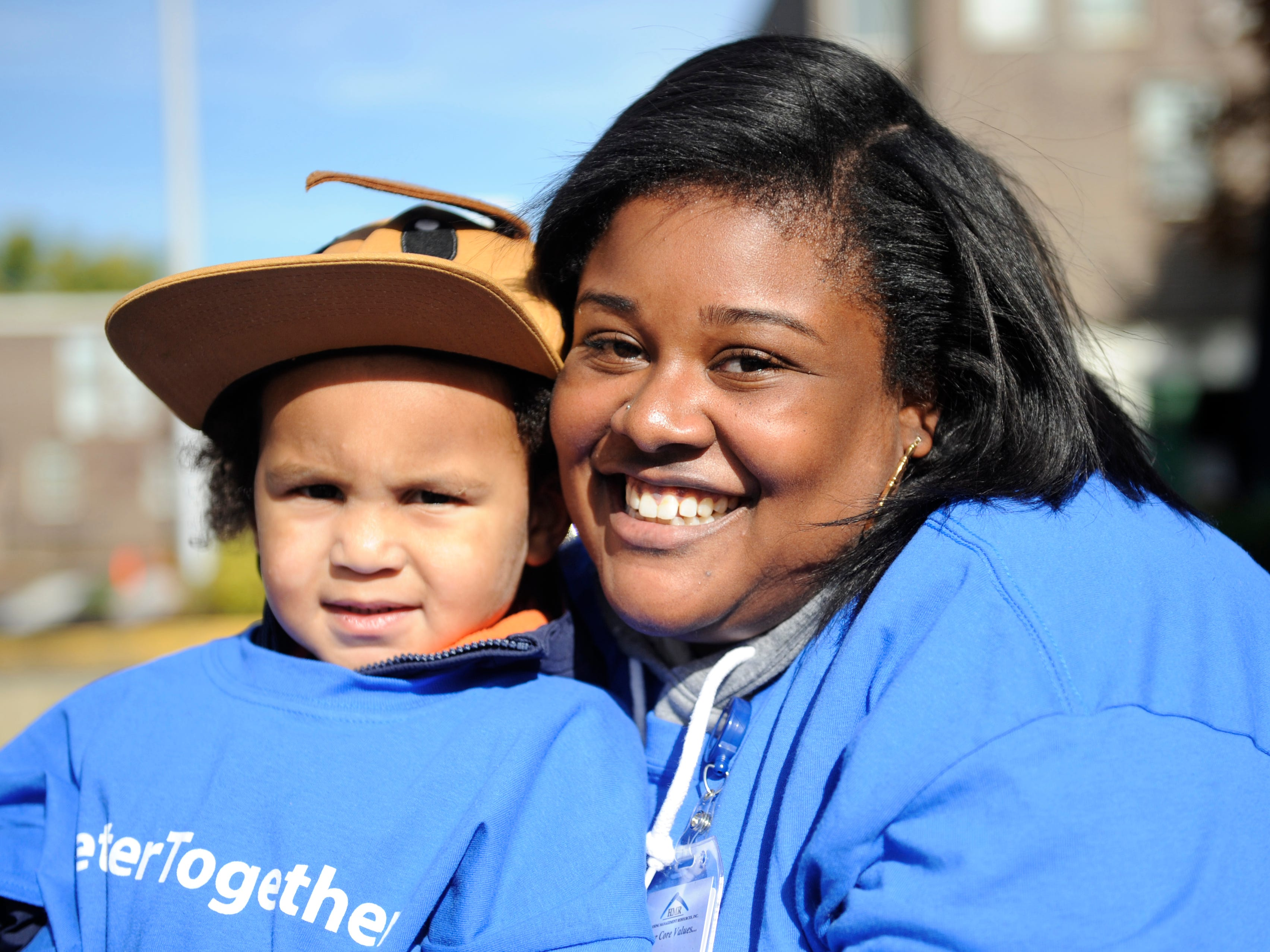 Kai Dubrey, Administrative Assistant at Oakview Apartments in Millville, posses for a picture with her child during a special community clean up event.