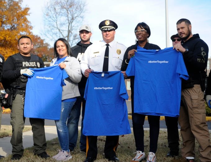 Millville Police Chief Jody Farabella (center) with members of his force, hold #BetterTogether shirts along with Oakview Apartments staff members, Tania Alvarado (left) and Jaclyn Garrett (right) during a community clean up event on the grounds of the complex.