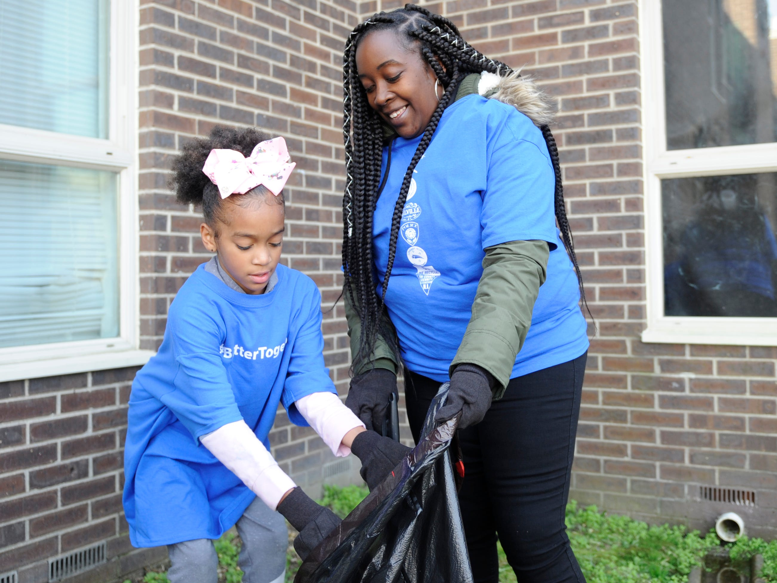 Oakview Apartments residents Dena Alsobrook (right) and daughter Miyasiah, 10, help with the  clean up efforts during a community event.