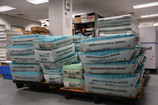 The Tulare County elections office has its work cut out with bins of mail and provisional ballots stacked high.