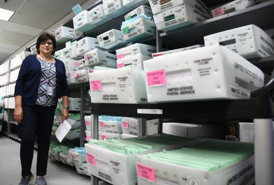 Registrar of Voters Michelle Baldwin in a roomful of ballots waiting to be processed.