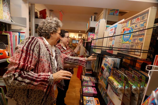 Paulene Greeman, owner of Anderson's Books in Larchmont, and Jeannette Rudoff, organize a display in the store's toy section Nov. 8, 2018. The store offers a range of toys for infants up to young adults.