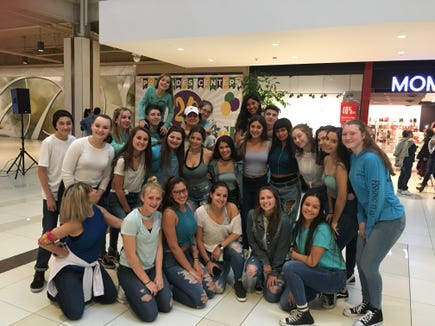 Adrias with participants for the Center for Safety and Change's Denim Day flash mob at the Palisades Center Mall.